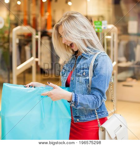 Concept Shopping. Portrait of beauty blonde woman in casual clothes surprised by purchases near shop in the shopping center. Indoor. Copy space