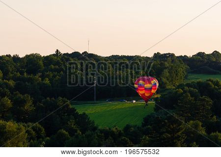 Colorful hot air ballon landing in a Wisconsin farm field in July