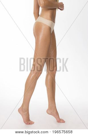 Tanned girl's legs and beige thongs body parts shot
