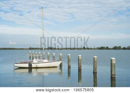 small sail boat moored in a lake in the netherlands
