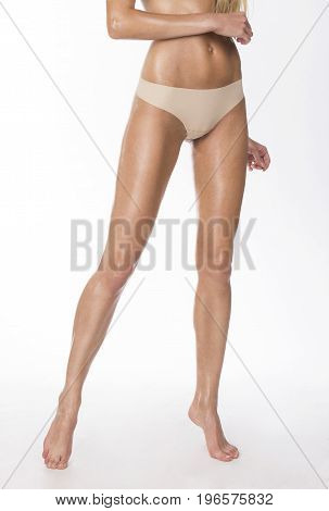 Skinny woman's legs and beige thongs, studio shot