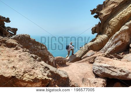 Photographer traveler climbs on a rock to take pictures of a beautiful natural look Iran's Hormuz Island in Persian Gulf Hormozgan Province southern Iran.