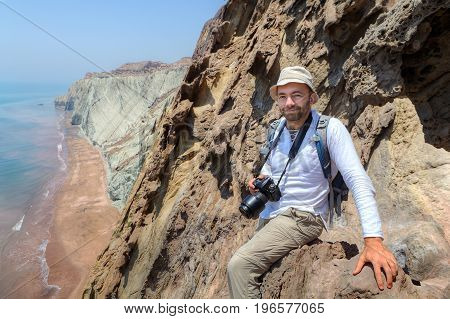 Pleased traveller with camera sits on a edge of a cliff Hormuz Island Hormozgan Province southern Iran.