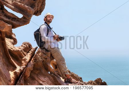 Pleased nature photographer is sitting on the edge of cliff Hormuz Island Hormozgan Province southern Iran.