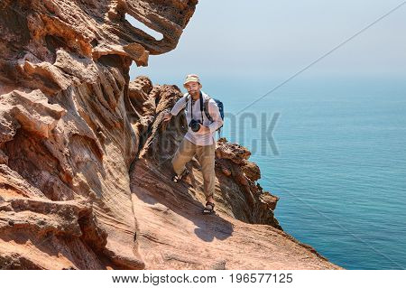 A mature traveler photographer climbs on rocks over the sea Hormuz Island Hormozgan Province Southern Iran.