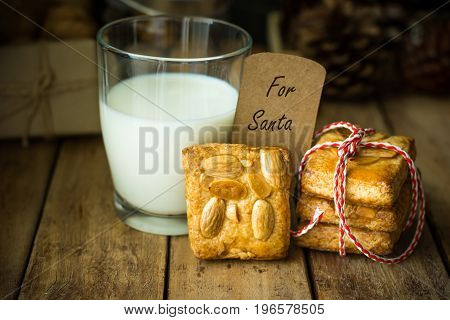 Stack of homemade almond Christmas cookies tied with red and white ribbon glass of milk note with written words for santa clause rustic style festive