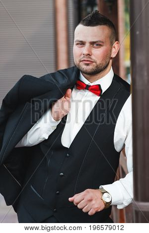 Young attractive businessman on vacation after business talks stylish man is holding his jacket on his shoulder hand with golden watch business concept look at the camera