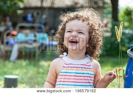 Portrait of a smiling little girl outdoors in summer