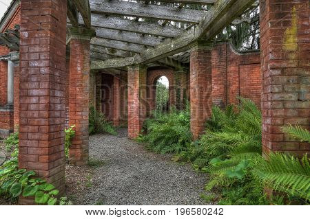 A gravel path through brick columns and green foliage