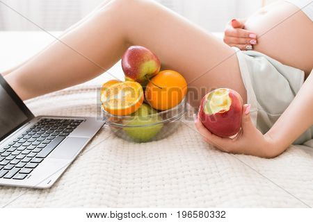 Pregnant woman eats apple and takes a break after chatting in laptop. Work and relax combining, fresh fruits and healthcare concept of special mother-to-be period