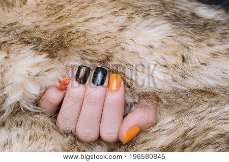 Beautiful female hand with orange and black nail art.