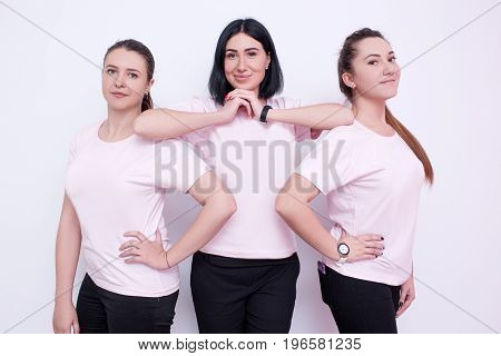 Three women in white t-shirts. Young friends, advertising on clothes, promo campaign, smiling hostesses, friendly team concept