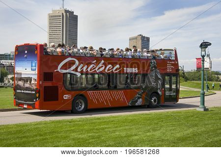 QUEBEC CANADA - AUGUST 20 2014: Sightseeing red tourist bus rides at the Parc des Champs-de-Bataille National Battlefields Park . Historic part of Quebec City in Canada