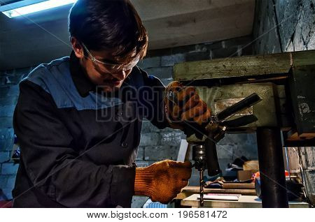 Apprentice Engineer Using Milling Machine at garage