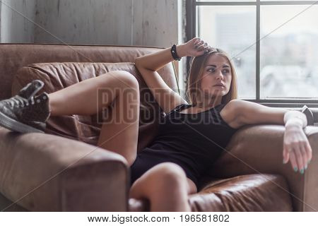 Sexy young woman relaxing reclining on a leather armchair in underwear and shoes in a room.