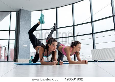 Two sportive girlfriends doing butt toning exercise performing donkey kicks on a mat in light modern fitness hall with big windows
