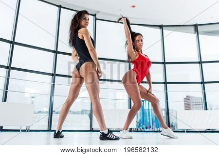 Two sexy young Caucasian women dancing in studio wearing swimsuits and trainers with panoramic windows in background.