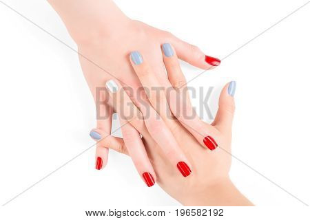 Woman connected hands with red and blue shellac nail polish. Isolated on white clipping path included
