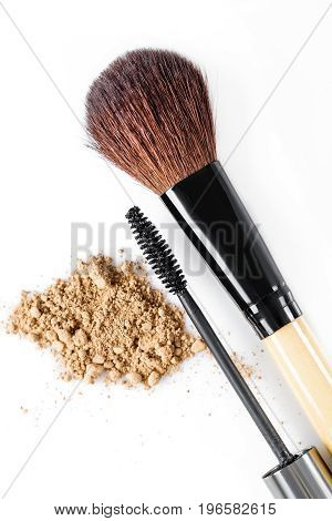 Mascara, beige powder for face and makeup brush on the white background. Natural makeup
