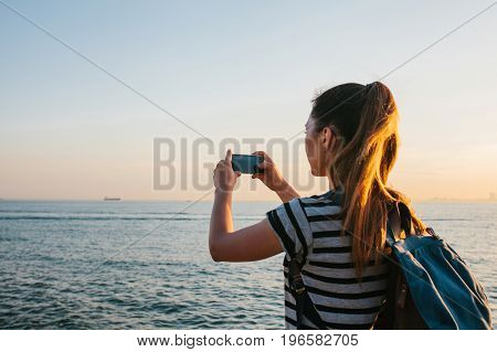 A young girl with a backpack pictures on the phone a beautiful view of the sea and the sunset. Picture for memory. Travel, vacation.