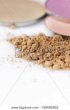 Beige powder for the face and round eye shadow on a white background. Natural make up.