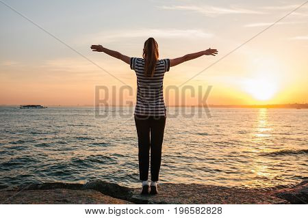 Young girl from the back raised her hands up against the sunset background next to the sea. Freedom, travel, vacation.