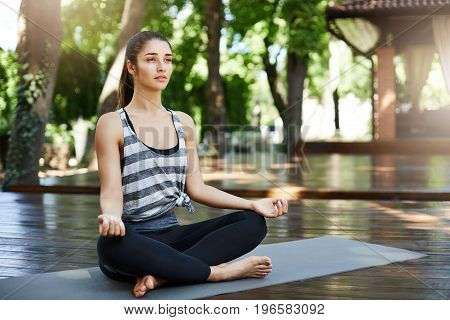 Young lady starting her morning yoga practice with a meditation and deep breath sitting in a temple. Healthy lifestyle concept.