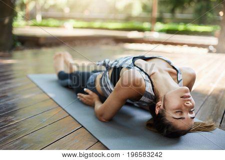 Young girl practicing matsyasana on a sunny summer day.