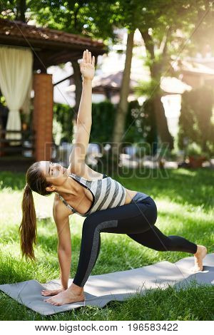 Lady at yoga practice in her backyard. utthita parsvakonasana or a similar asana. Healthy lifestyle concept.
