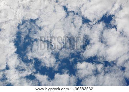 Blue sky and a lot of cumulus clouds a little bird in the sky