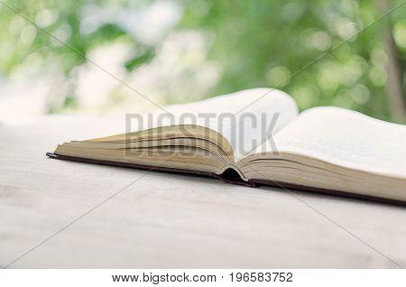Open book in front of an open window.