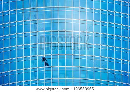 Industrial climber wash the windows of modern skyscraper. Blue toned image