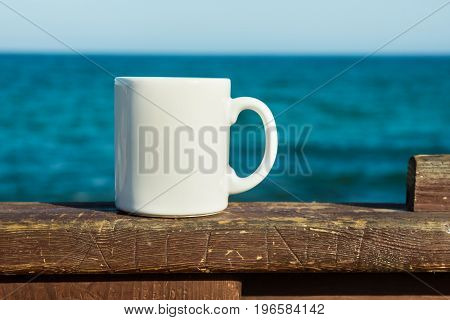 White mug mock up empty space for artwork text standing on wood plank turquoise sea clear blue sky horizon sunlight nature