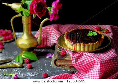 raspberry quiche with mint and roses on a bronze platter