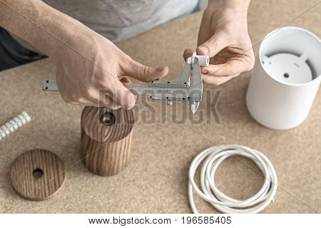 Process of measuring in the workshop. Man is using a caliper on the white metal detail. Under his hands there are wooden and metal cylindrical billets, cable, connector. Closeup. Horizontal.