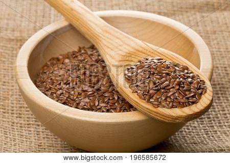 Raw unprocessed linseed or flax seed in wooden bowl and wood spoon on burlap background
