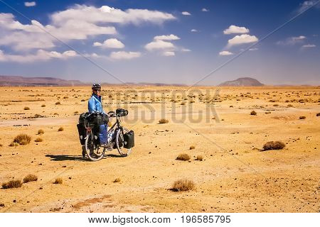Woman cycling through the dry, desolate, empty countryside towards Oruro in central Bolivia