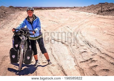 Woman cyclist struggling and pushing her bike on the sandy corrugated road in Altiplano in Bolivia