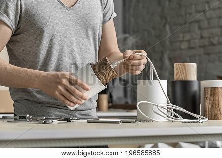 Lamp assembling in the workshop. Man holds a white lamp with a wooden part per the cable. On the table there are other lamp billets, different wrenches, screws and bushings. Closeup. Horizontal.