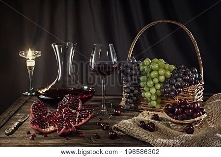Romantic mood red wine in a glass grapes pomegranate.