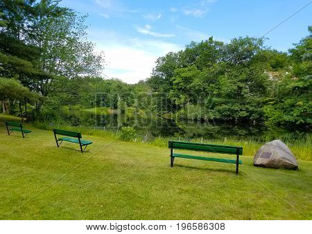Three benches and a rock waiting by the river bank