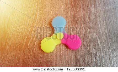 Playing with the colorful Fidget Spinner. Toy spinner in hand.Sun effect.