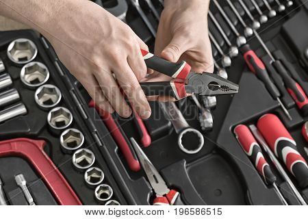 Black toolbox on the light tabletop in the workshop. Man holds a pliers above it. Inside the toolbox there are black-red wrenches, screwdrivers, spanners and different nozzles. Closeup. Horizontal.