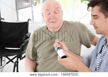 Young male volunteer giving medicine to senior man in light room
