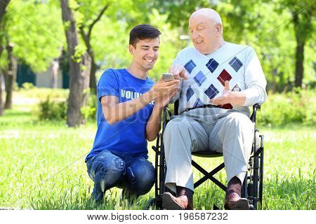 Young male volunteer and senior man on wheelchair with mobile phone outdoors