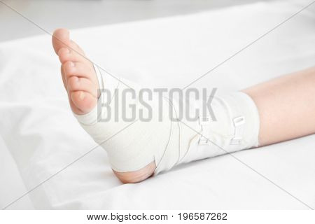 Young woman with bandaged leg in clinic, closeup
