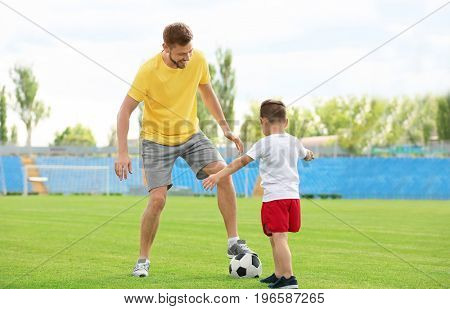 Dad and son playing football together in stadium