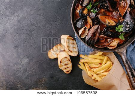 Mussels with sauce in a frying pan. French fries and croutons. Copy space. view from above