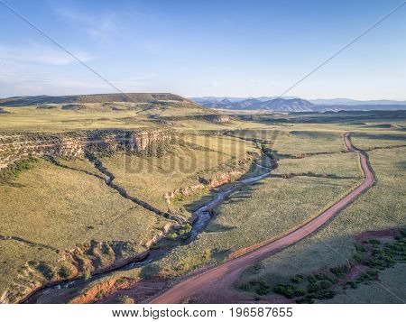 northern Colorado foothills aerial view - dirt road and whitewater stream n summer scenery