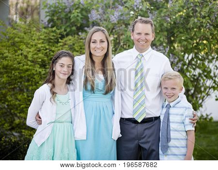Beautiful Young Family Portrait outdoors. Standing and wearing formal clothing and smiling together in a beautiful green setting